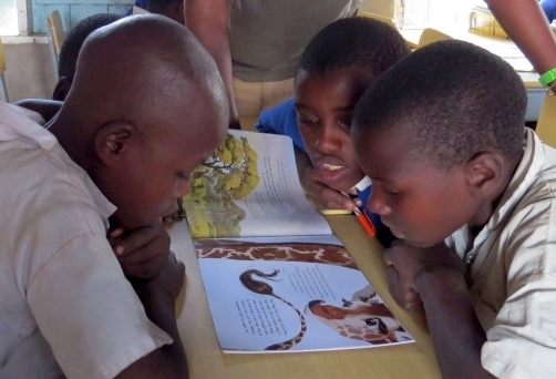 Children reading giraffe-themed education materials_Wild Nature Institute